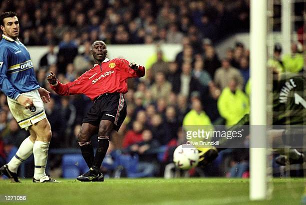 Andy Cole of Manchester United slots the ball past the outstretched fingers of Everton keeper Thomas Myrhe to score in the FA Carling Premiership...
