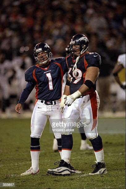 Kicker Jason Elam of the Denver Broncos walks with teammate Mark Schlereth during a game against the Jacksonville Jaguars at Mile High Stadium in...