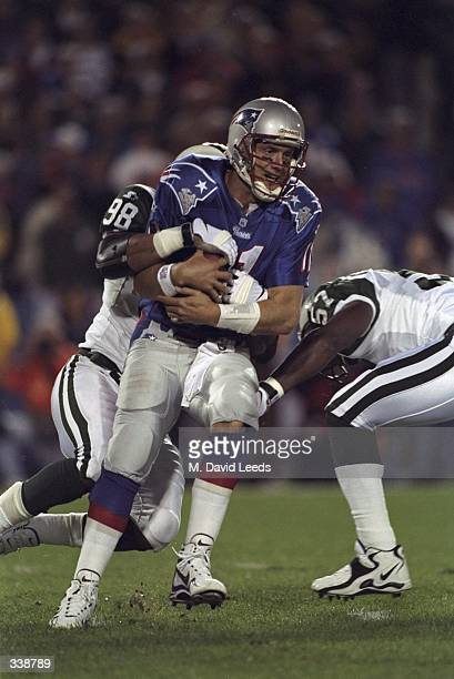 Quarterback Drew Bledsoe of the New England Patriots is sacked by Anthony Pleasant of the New York Jets during a game at the Foxboro Stadium in...
