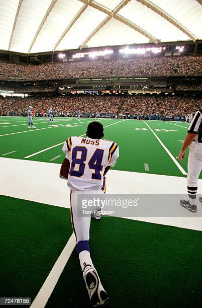 Randy Moss of the Minnesota Vikings kneels on the sidelines during a game against the Detroit Lions at the Pontiac Silverdome in Pontiac Michigan The...
