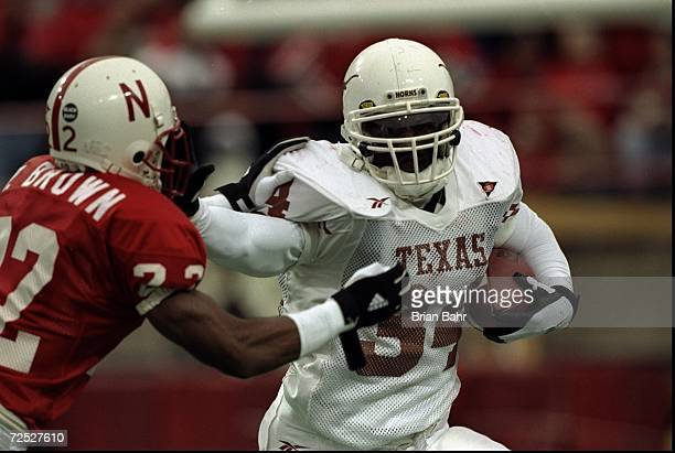 Ricky Williams of the Texas Longhorns grips the ball as he pushes Ralph Brown of the Nebraska Cornhuskers at Memorial Stadium in Lincoln Nebraska...