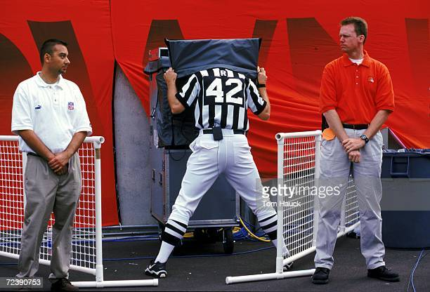 A referee stands under a black shield as he watches the instant replay during a game between the New England Patriots and the Cleveland Browns at the...