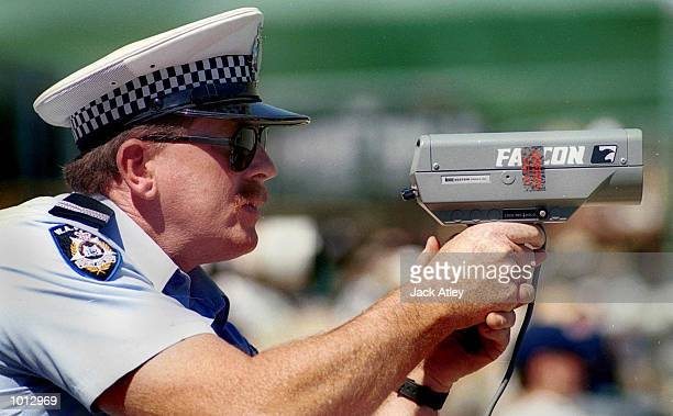 A Western Australian policeman aims his speed radar gun at the wicket trying to determine the speed of Pakistan fast bowler Shoaib Ahktar during the...