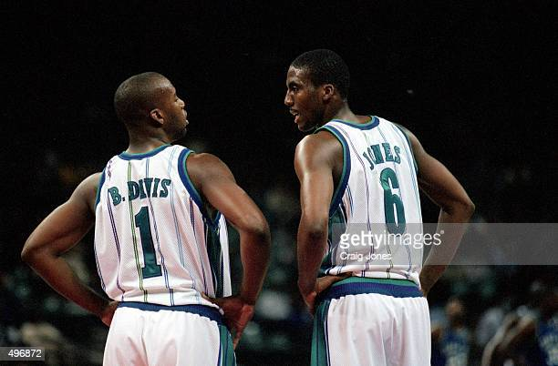 Baron Davis of the Charlotte Hornets talks to teammate Eddie Jones during the game against the Dallas Mavericks at the Charlotte Coliseum in...