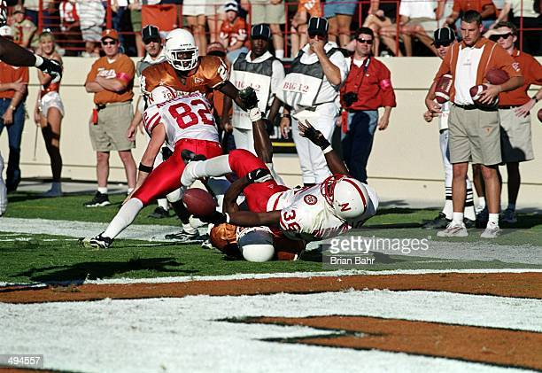 Correll Buckhalter of the Nebraska Cornhuskers fumbles the ball at the one yard line as he trips over Ahmad Brooks of the Texas Longhorns during the...