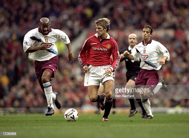 David Beckham of Manchester United gets away from Dion Dublin of Aston Villa during the FA Carling Premiership match at Old Trafford in London United...