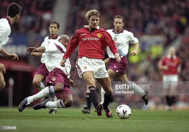 David Beckham of Manchester United is challenged by Dion Dublin of Aston Villa during the FA Carling Premiership match at Old Trafford in London...
