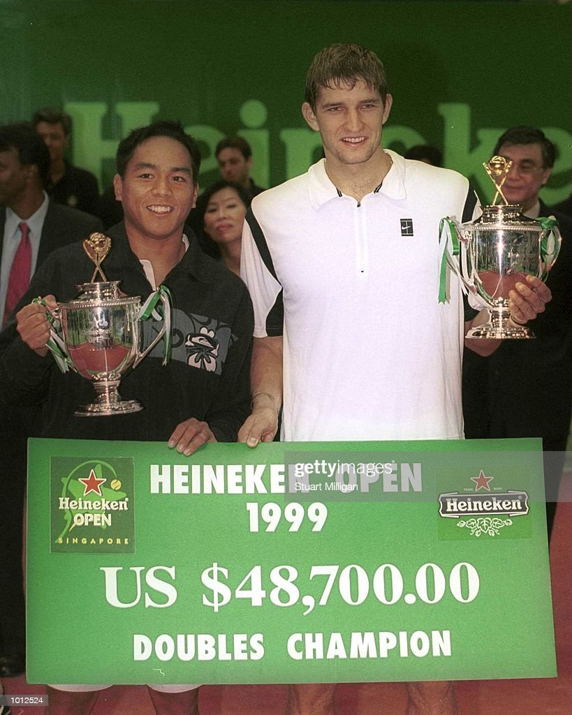 Eric Taino of the USA (left) and his partner Max Mirnyi of Bulgari parade their doubles trophy and cheque after their final against Mark Woodforde and Todd Woodbridge, of Australia at the Heineken Singapore Tennis Open, played at the Singapore Indoor Stadium, Singapore. Taino and Mirnyi won 6-3, 6-4. Mandatory Credit: Stuart Milligan/Allsport
