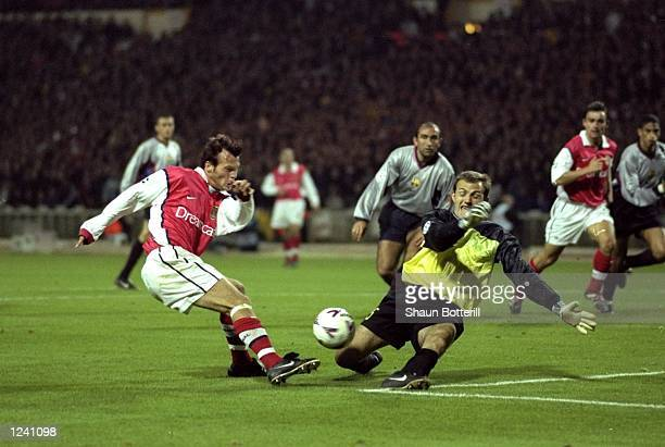 Fredrik Ljungberg of Arsenal has his shot blocked by the legs of Barcelona ''keeper Francesc Arnau during the Champions League Group B match played...