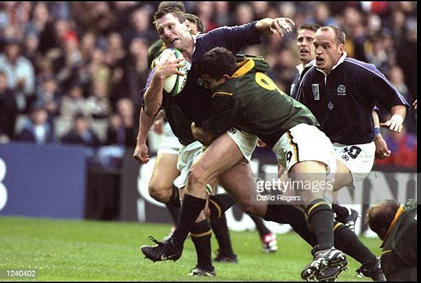 Gary Armstrong of Scotland is tackled by Joost Van Der Westhuizen of South Africa during the Rugby World Cup match played at Murrayfield in Edinburgh...