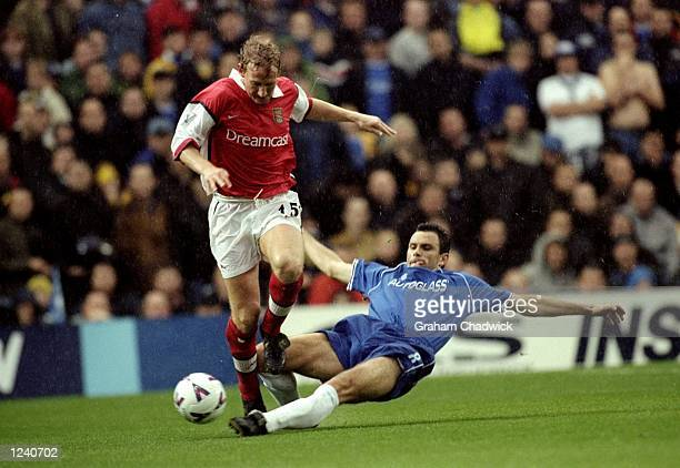 Gustavo Poyet of Chelsea slides in to tackle Ray Parlour of Arsenal during the FA Carling Premier League match played at Stamford Bridge London The...