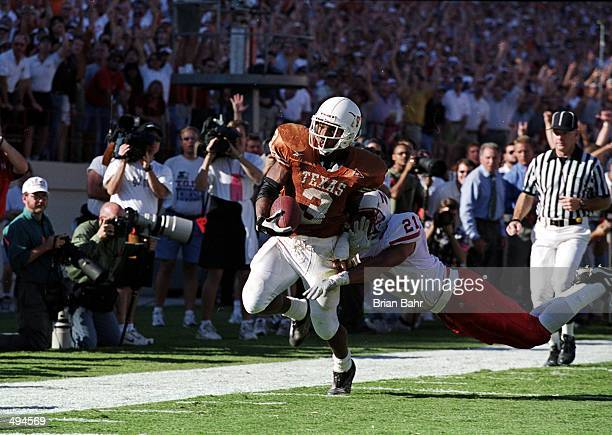 Hodges Mitchell of the Texas Longhorns runs with the ball as Mike Brown of the Nebraska Cornhuskers tries to pull him down during the game against at...