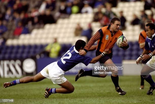 Jamie Mayer of Scotland hands off Terry Fanolua of Samoa during the Rugby World Cup quarterfinal playoff match at Murrayfield in Edinburgh Scotland...