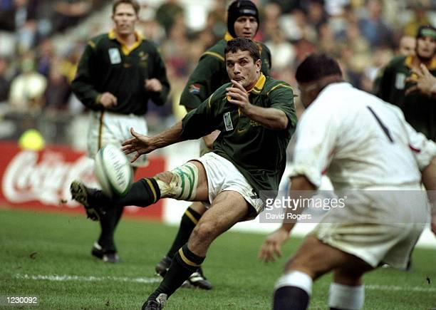 Joost van der Westhuizen of South Africa kicks over Jason Leonard of England in the Rugby World Cup quarterfinal match at the Stade de France in...