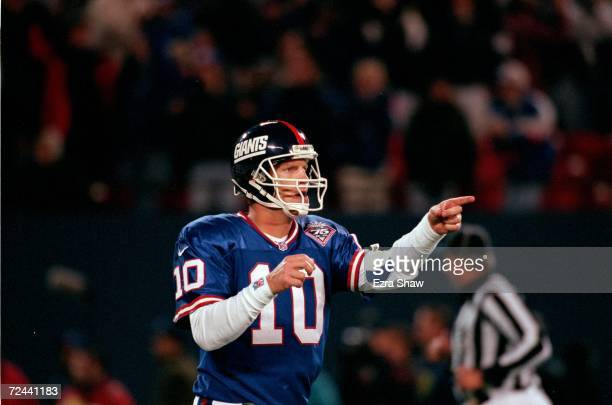 Kent Graham of the New York Giants points on the field during a game against the Dallas Cowboys at the Giants Stadium in East Rutherford New Jersey...