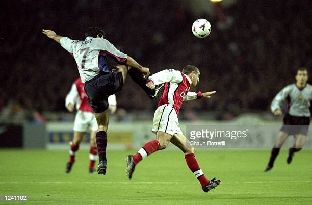 Luis Figo of Barcelona tussles with Nigel Winterburn of Arsenal during the Champions League Group B match played at Wembley Stadium London The game...