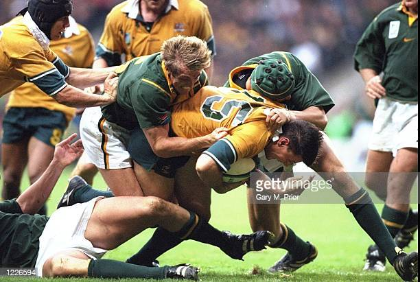 Matt Burke of Australia is tackled by Percy Montgmerie of South Africa during the SemiFinal of the Rugby World Cup played at Twickenham in London...