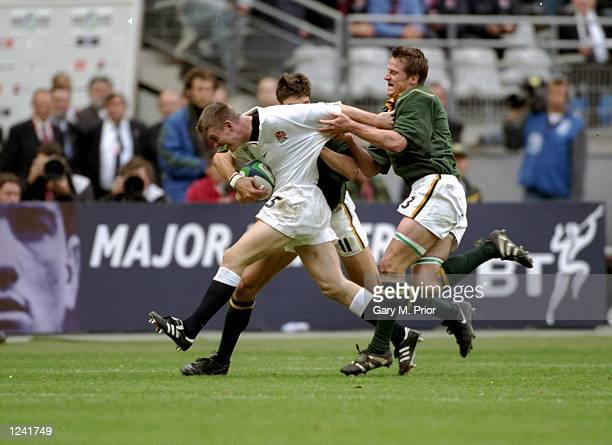 Matt Perry of England is held by Robbie Fleck of South Africa in the Rugby World Cup quarterfinal match at the Stade de France in Paris South Africa...