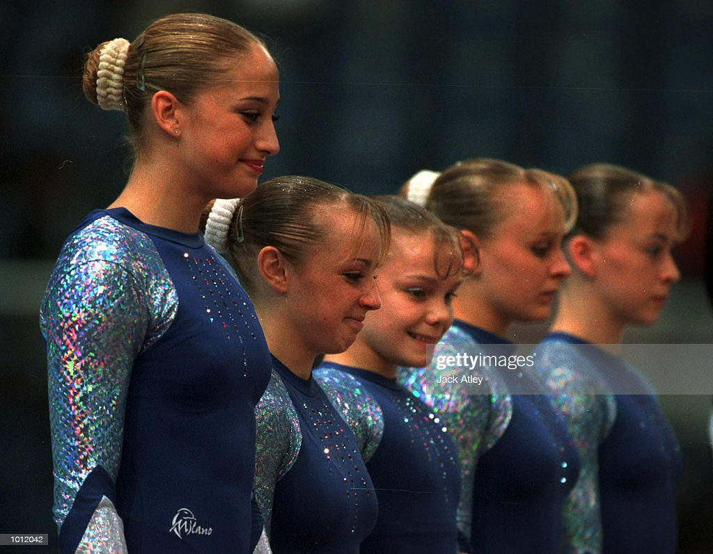 Natalie Lucitt and Sharna Murray (second left) of Great Britain begin to laugh whilst other team members look on, as they face the judges, just prior to their uneven bars routine in the qualifying round at the 1999 Tianjin World Gymnastics Championships, Tianjin, China. Mandatory Credit: Jack Atley/ALLSPORT
