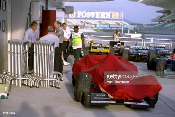 Ron Dennis and Charlie Whiting of the Maclren Mercedes team discuss the race beside the illegal Ferrari after the Formula One Malaysian Grand Prix at...