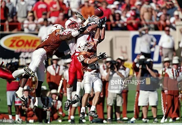 Ryan Nunez and Kwame Cavil of the Texas Longhorns go up for a hail mary pass in the first half of the game against the Nebraska Cornhuskers at the...