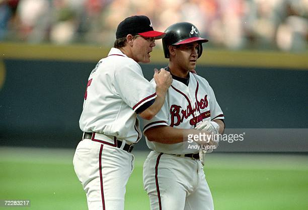 Third base coach Ned Yost of the Atlanta Braves congratulates Bret Boone on his triple base hit during the game against the Houston Astros at Turner...