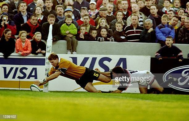 Tom Bowman of Australia dives over to score a try during the 1999 Rugby World Cup Pool E match against the USA at Thomond Park in Limerick Ireland...