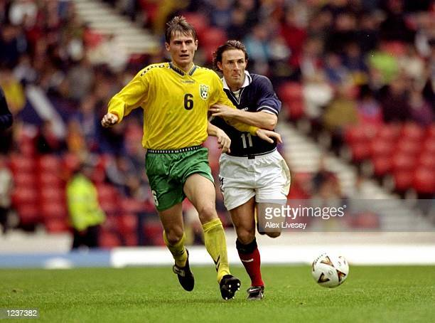Tomas Zvirgzdauskas of Lithuania holds off Gary McSwegan of Scotland during the European Championships Group 9 qualifier against Lithuania at Hampden...