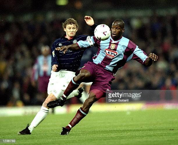 Ugo Ehiogu of Aston Villa shields the ball from Ole Gunnar Solskjaer of Manchester United during the Worthington Cup Round 3 match played at Villa...