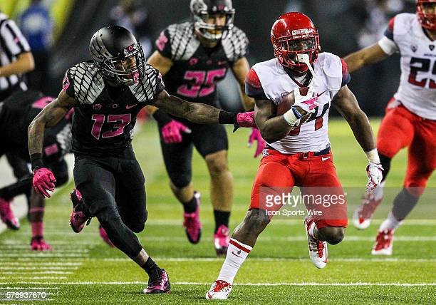 Arizona Wildcats running back Terris JonesGrigsby tries to avoid Oregon Ducks defensive back Troy Hill during the game between the Arizona Wildcats...