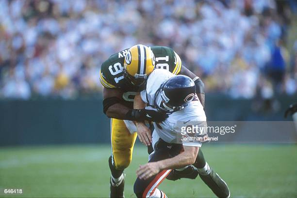 John Thierry of the Green Bay Packers tackles Cade McNown of the Chicago Bears during the Bears v Packers game in which the Bears defeated the...