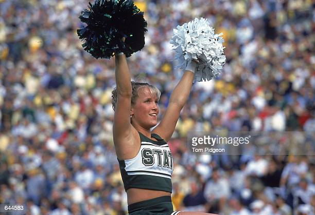 A Michigan State Spartans cheerleader cheers on the sidelines during the game against the Michigan Wolverines at the Michigan Stadium in Ann Arbor...