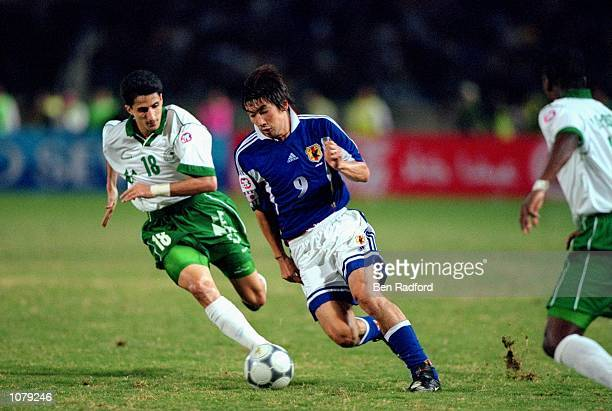 Akinori Nishizawa of Japan goes past Nanaf Al Temyat of Saudi Arabia during the Asian Cup Final match played in Beirut Lebanon Japan won the game and...