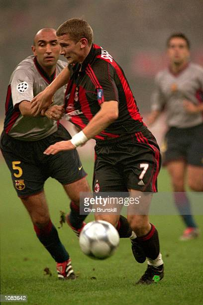 Andrei Shevchenko of AC Milan holds off Fernandez Abelardo of Barcelona during the UEFA Champions League match at the San Siro in Milan Italy The...