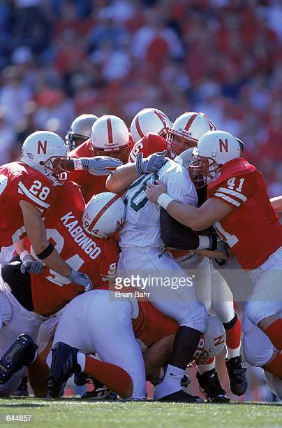 Bobby Darnell of the Baylor Bears carries the ball as he is swarmed and is tackled by Rod Baker and Patrick Kabongo of the Nebraska Cornhuskers at...