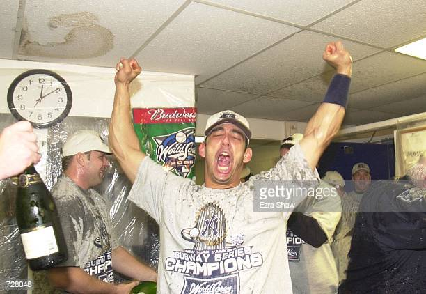 Catcher Jorge Posada of the New York Yankees celebrates in the locker room after defeating the New York Mets 42 in Game 5 to clinch their third...