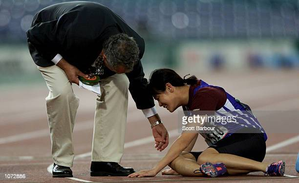 Chun Lai Yu of Hong Kong is helped by an official after falling after finishing the Womens 400M T36 Final held at Olympic Park during the Sydney 2000...