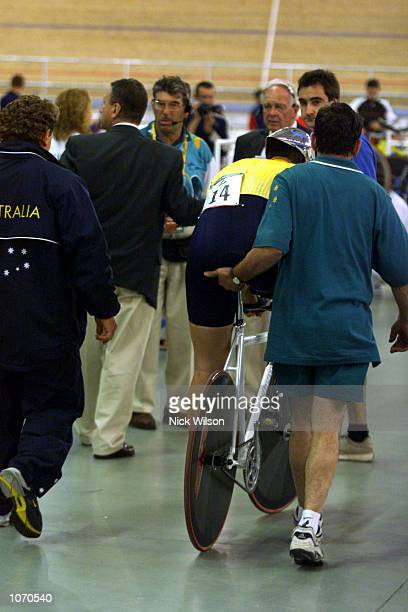 Daniel Polson of Australia is helped from the arena after he stumbled out of the Mixed 1 Kilometre Time Trial LC2 during the Sydney 2000 Paralympics...