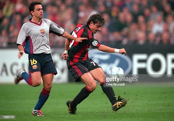 Francesco Coco of AC Milan is challenged by Xavi of Barcelona during the UEFA Champions League match at the San Siro in Milan Italy The match was...