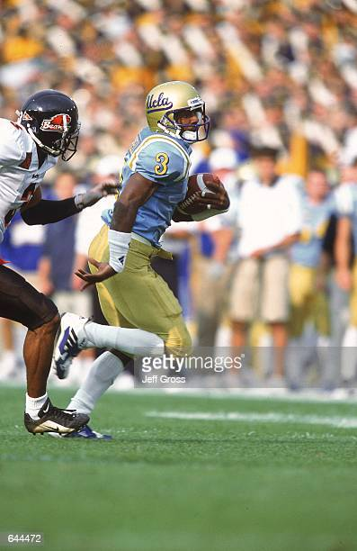 Freddie Mitchell of the UCLA Bruins runs with the ball chased by Keith HeywardJohnson of the Oregon State Beavers during the gameat the Rose Bowl in...