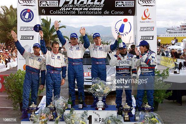 Gilles Panizzi of the Peugoet team celebrates on the podium after winning the Corsica Rally Francois Delecour of the Peugoet team finished Second and...