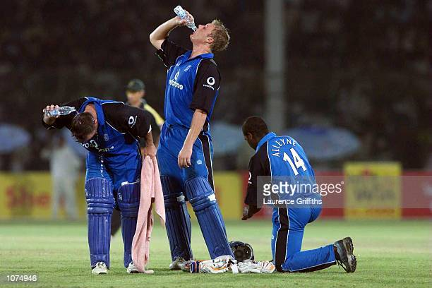 Graham Thorpe and Andrew Flintoff of England cool off with water during the first One Day International against England at the National Stadium...