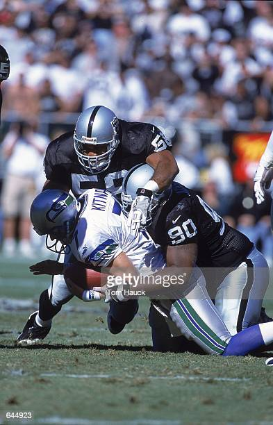 Jon Kitna of the Oakland Raiders gets tackled by Elijah Alexander and Grady Jackson of the Seattle Seahawks during the game at the Network Associates...