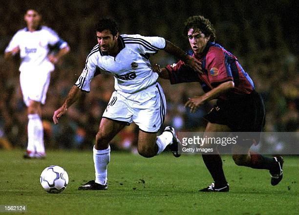 Luis Figo of Real Madrid gets away from Carles Puyol of Barcelona during the Spanish Primera Liga match between Barcelona and Real Madrid at the Nou...