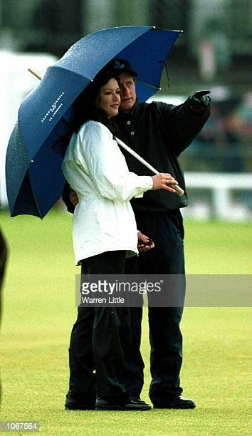 Michael Douglas points out an area of the course for Cathrine Zeta Jones during the ProAm of the Alfred Dunhill Cup played on the Old Course at St...