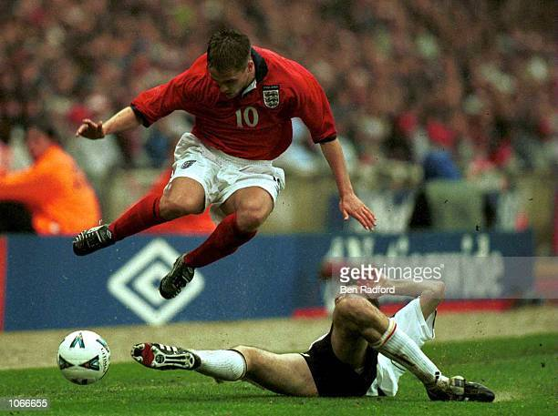 Michael Owen of England jumps the tackle of Dietmar Hamann of Germany during the match between England and Germany in the European Group Nine World...