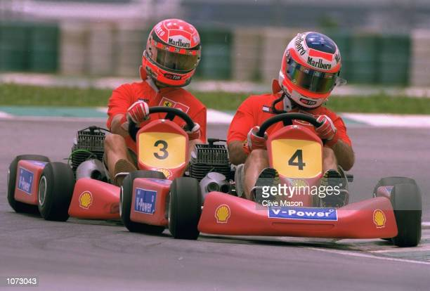 Michael Schumacher of Germany and Ferrari races with Rubens Barrichello of Brazil and Ferrari in a GoKart after the Malaysian Formula One Grand Prix...