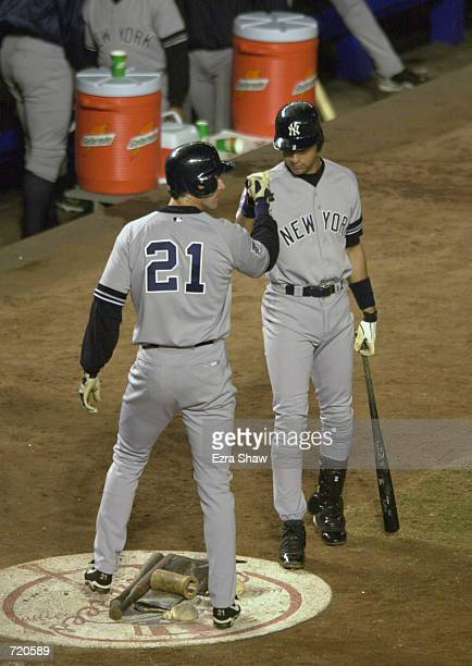 Outfielder Paul O''Neill of the New York Yankees is congratulated by Derek Jeter after scoring on a Scott Brosius sacrifice in the second inning...
