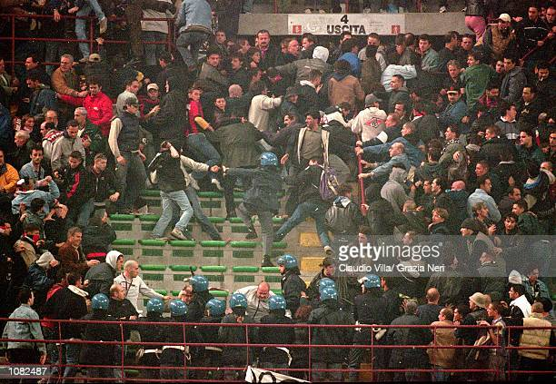 Police control rival fans during the Italian Serie A game between AC Milan and Juventus played at the San Siro Stadium in Milan Italy The game ended...
