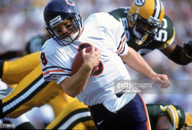 Quarterback Cade McNown of the Chicago Bears tucks the ball as he scrambles during a game against the Green Bay Packers at Lambeau Field in Green Bay...